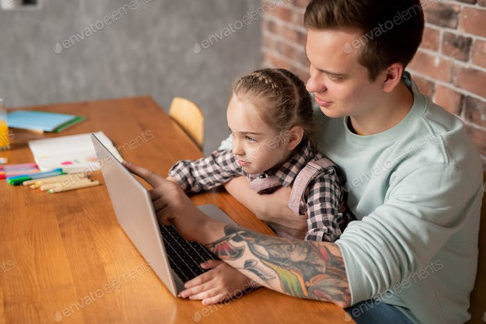 Young father using learning app on laptop