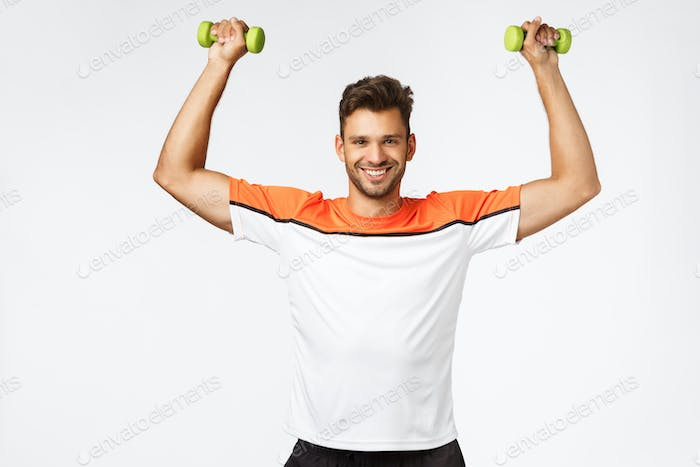 Sport and gym membership promo. Satisfied handsome muscular guy with bristle in sportswear lift
