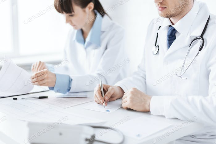 doctor and nurse writing prescription paper