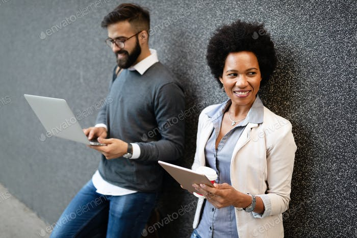 Happy businesspeople using technology devices gadgets near wall of modern building