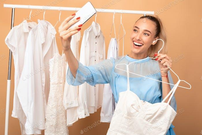 Glückliche Frau unter Selfie stehen in der Nähe von Rack mit Kleidung