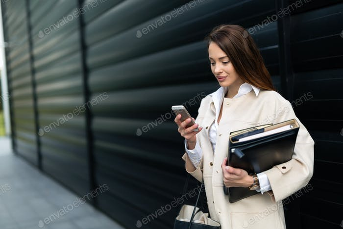 Attractive and beautiful businesswoman looking at cellphone