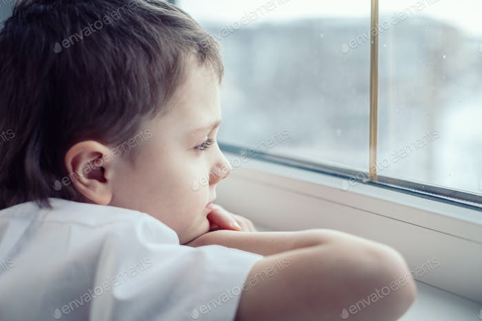 sad little boy sitting near the window