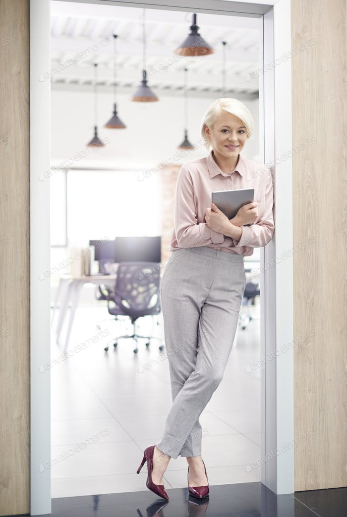 Smiling owner of office standing in doorway