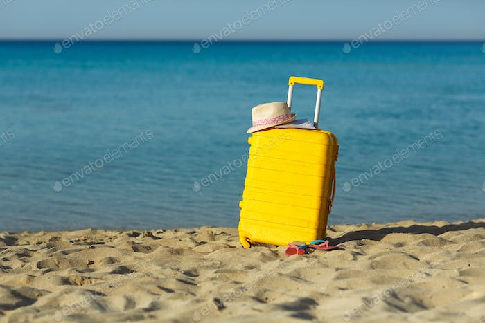 Travel holiday vacation suitcase with map, straw hat and beach s