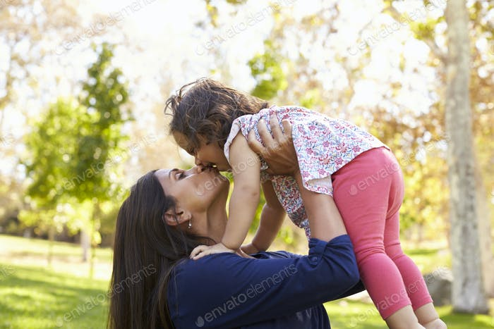 Mixed race Asian mum kissing her young daughter in park