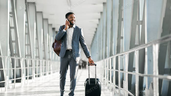 Cheerful Black Businessman Chatting On Phone Walking In Airport, Panorama