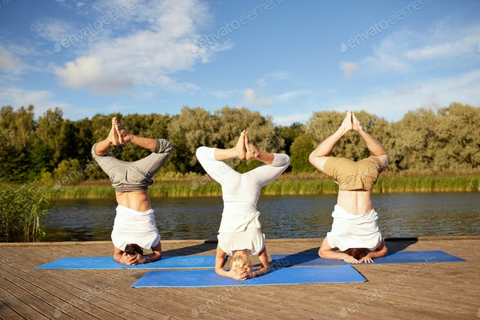 people making yoga headstand on mat outdoors