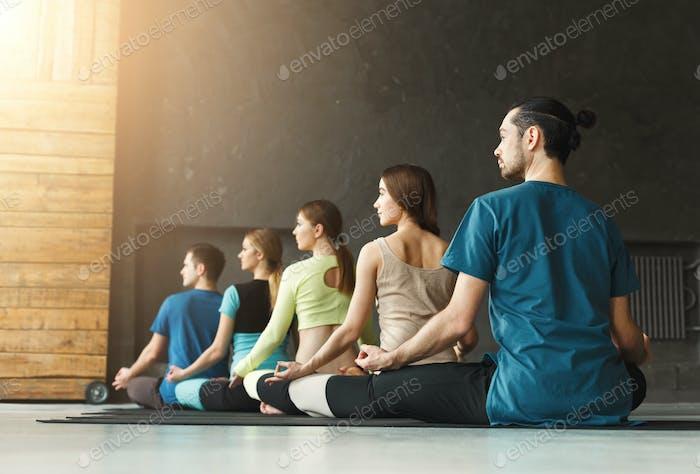 Junge Frauen und Männer in Yoga-Klasse, Entspannung Meditation Pose