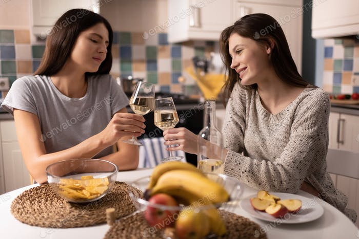 Female friends proposing toast during alcohol party