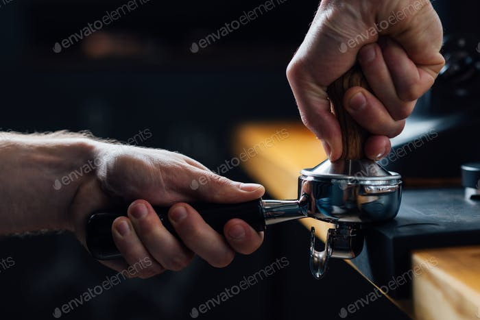 tempering coffee in portafilter on a dark background