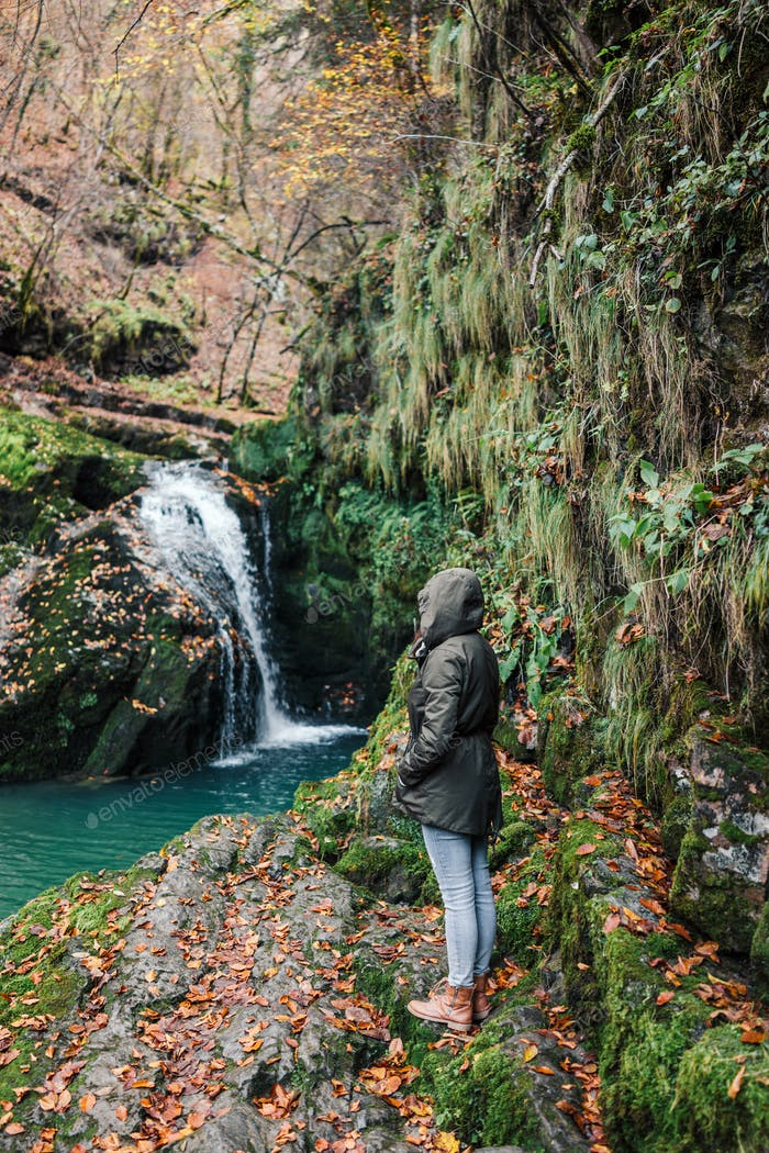Girl in a jacket by the waterfall