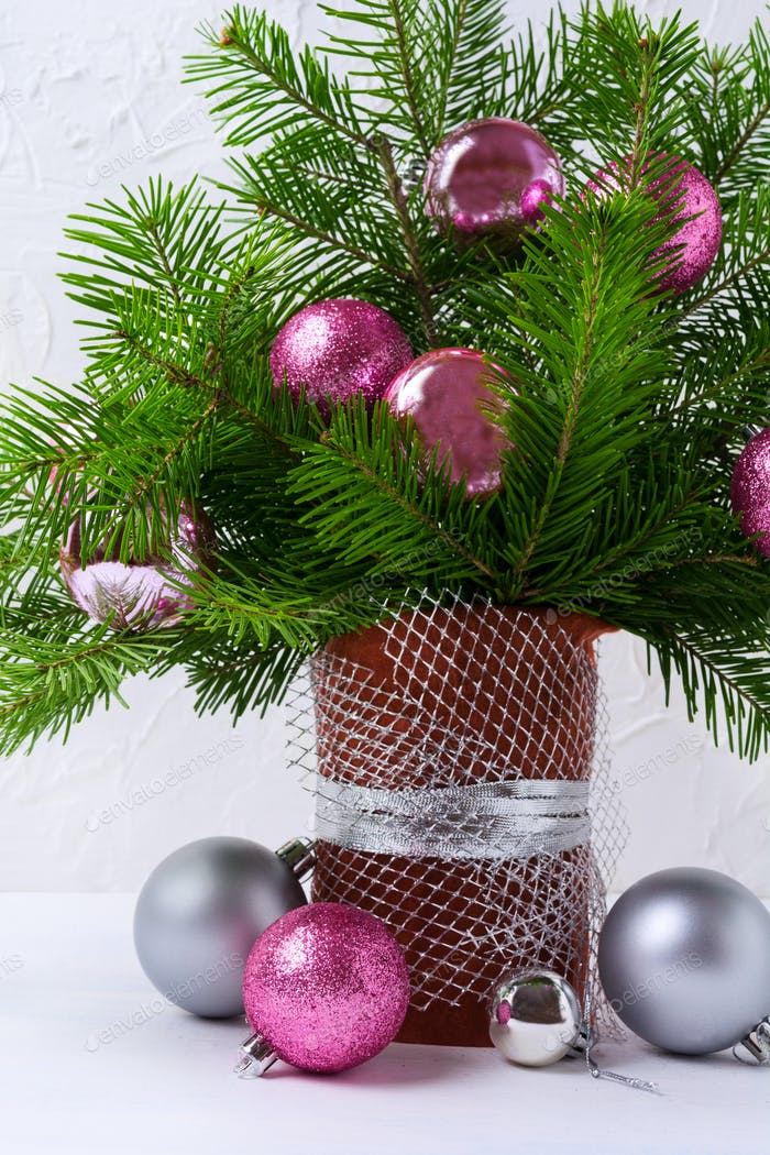 Christmas centerpiece with pink and silver baubles in brown vase