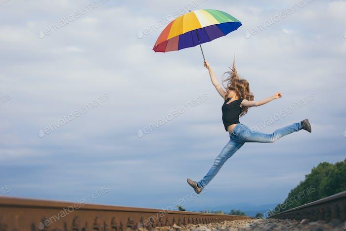Teen Mädchen mit Regenschirm springen auf der Eisenbahn zur Tageszeit.