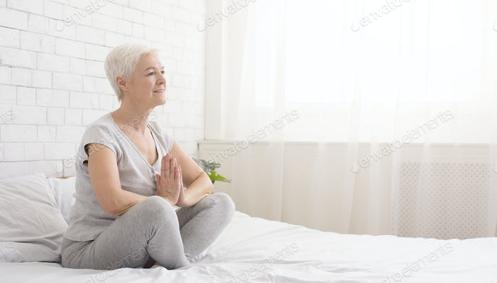 Young caucasian woman practicing yoga in bed