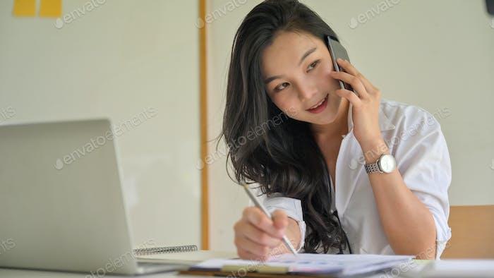 Mujeres de negocios jóvenes en el teléfono para coordinar en la oficina.