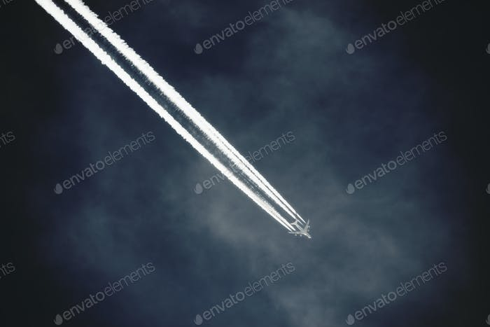 A jet with a clear condensation or vapour trail or contrail across a dark blue sky.