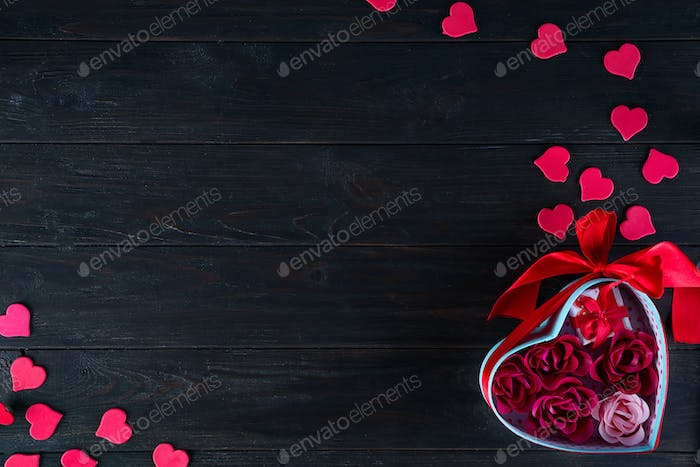 Valentines background with red hearts shaped and bouquet rose in gift box on dark wooden background