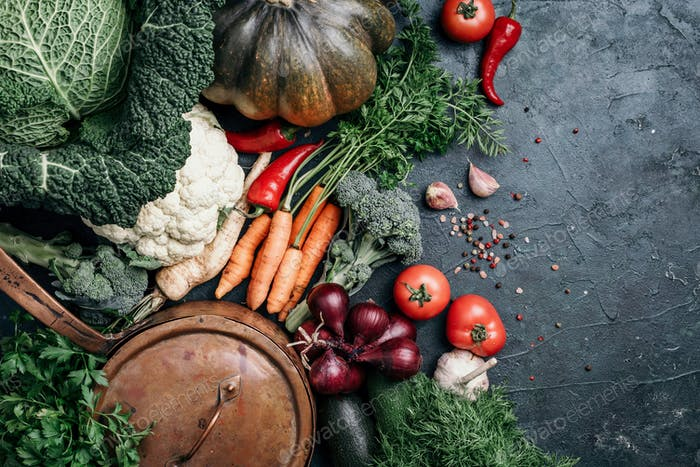 Healthy, clean food cooking and eating concept. Copper pan, colorful autumn vegetables on dark