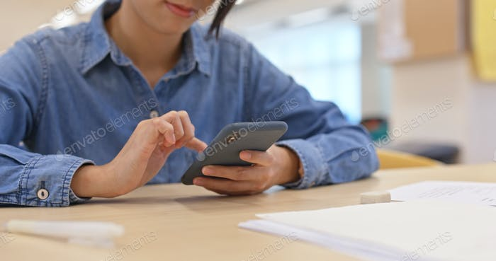 Woman use of mobile phone in the study room