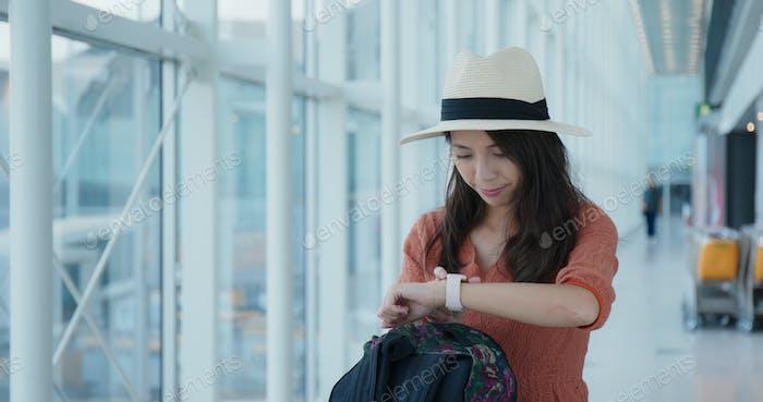 Mujer comprobar la hora en el reloj inteligente en el aeropuerto