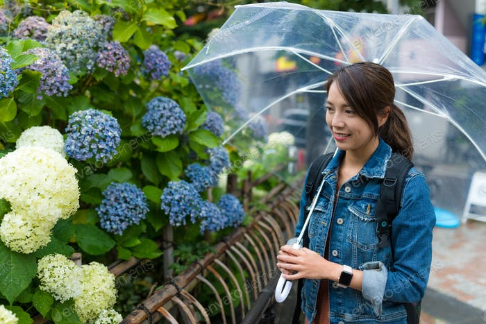 Woman look at the flower at rain day