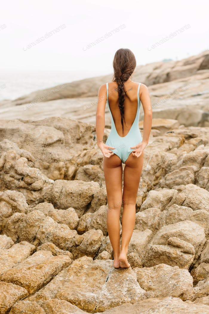 Beautiful girl in blue swimsuit walk on big stone.