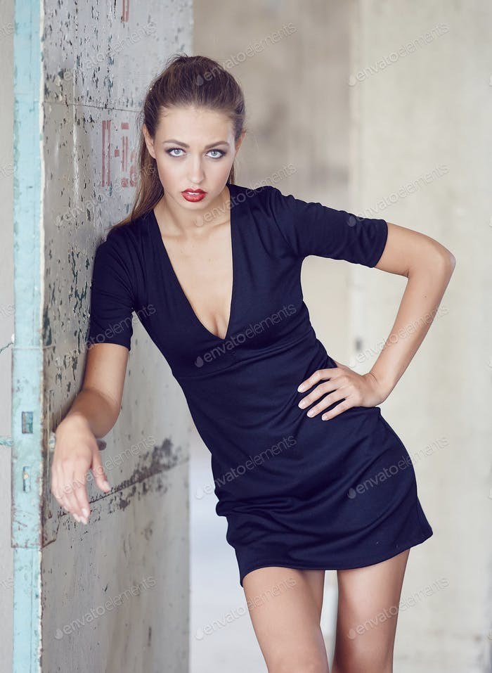 A young woman in a black dress posing.