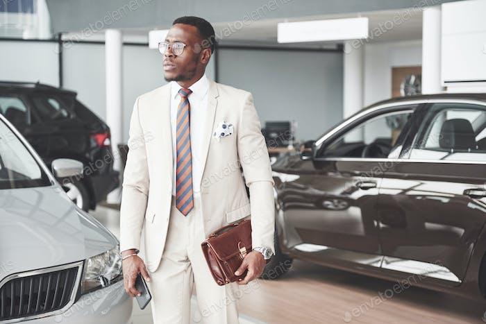 Junger schwarzer Geschäftsmann auf Auto-Salon-Hintergrund. Miet- und Mietkonzept