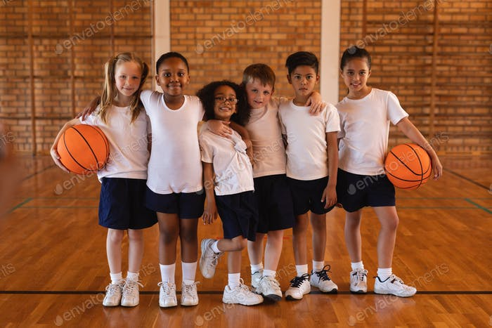 Front view of schoolkids standing and looking at camera at basketball court in school