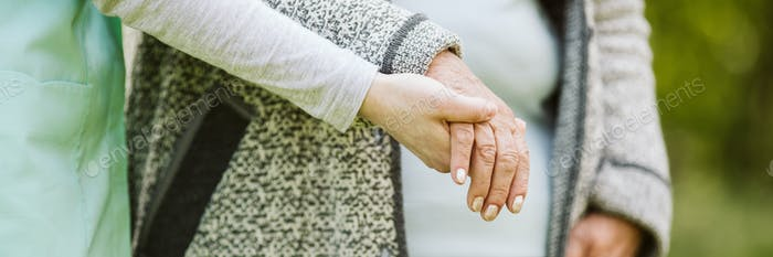 Young hand holding elder one. Help for the elder woman