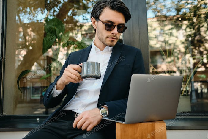 Young stylish man in jacket and sunglass drinking coffee dreamily working on laptop at street cafe