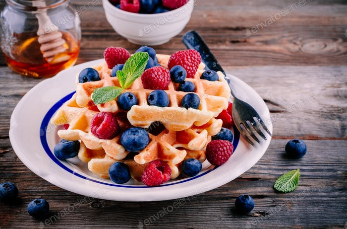 Fresh homemade belgian waffles with blueberries and raspberries for breakfast