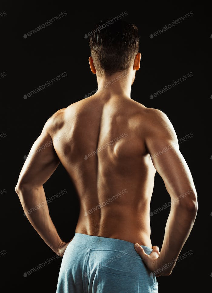 Athletic man showing his back on the black background