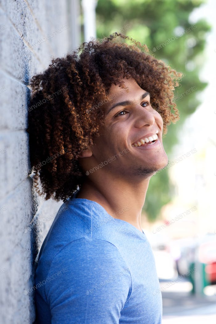 happy young man leaning against wall and laughing
