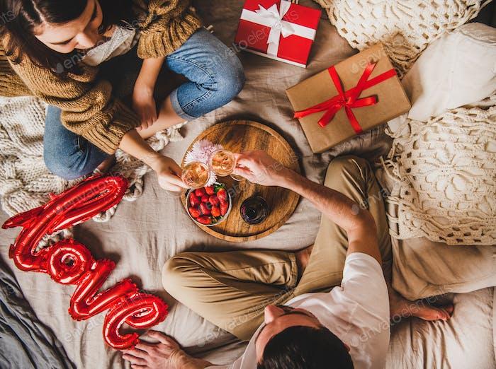 Junges Paar sitzen im Bett, geben Geschenke trinken Rose Champagner