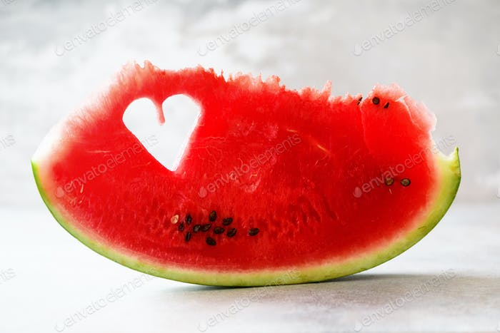 Piece of watermelon with heart shape on grey concrete background. Copy space. Flat lay. Greeting