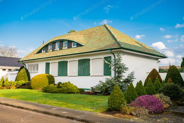 Facade of luxury detached house with beautiful garden