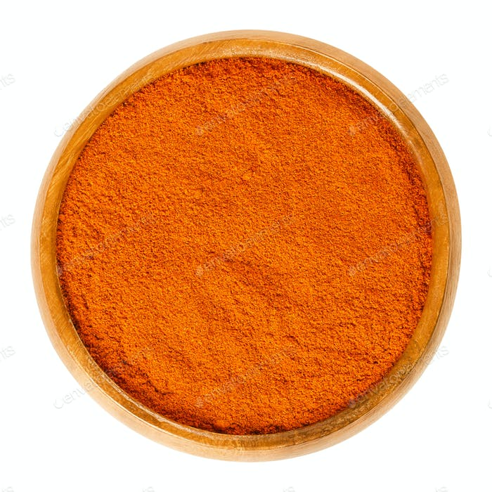 Cayenne pepper powder in wooden bowl over white