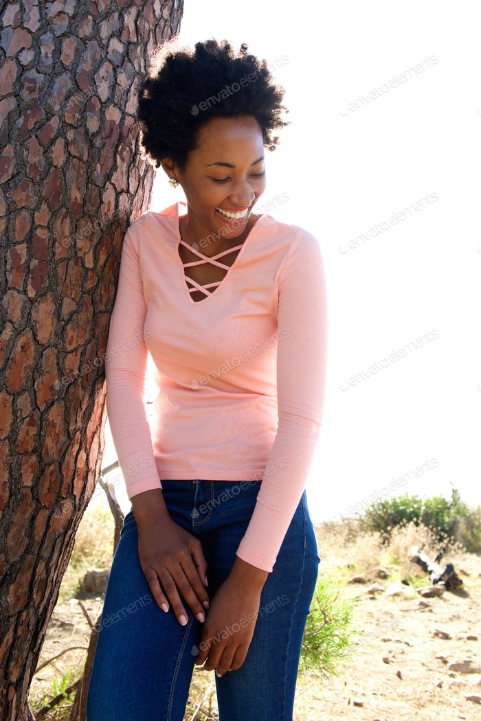 Attractive young african woman leaning to a tree