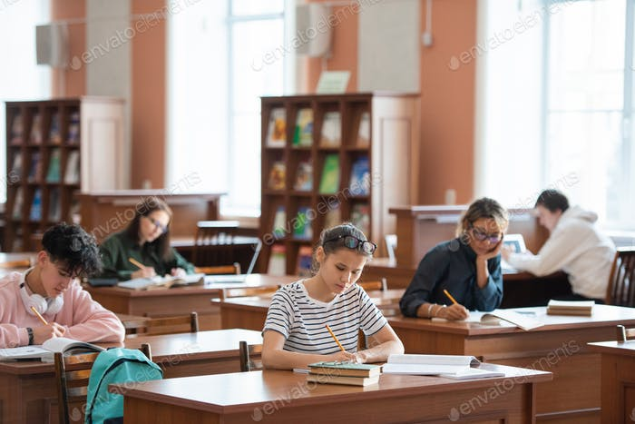 Several college students making notes while preparing for seminar