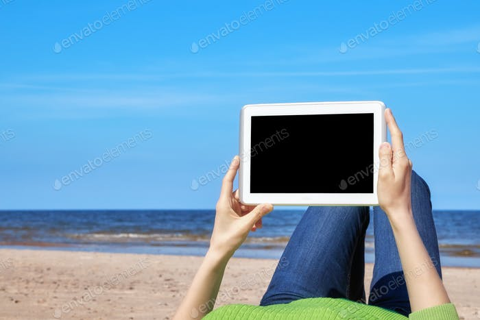 Close up picture of female hands with tablet computer on a beach