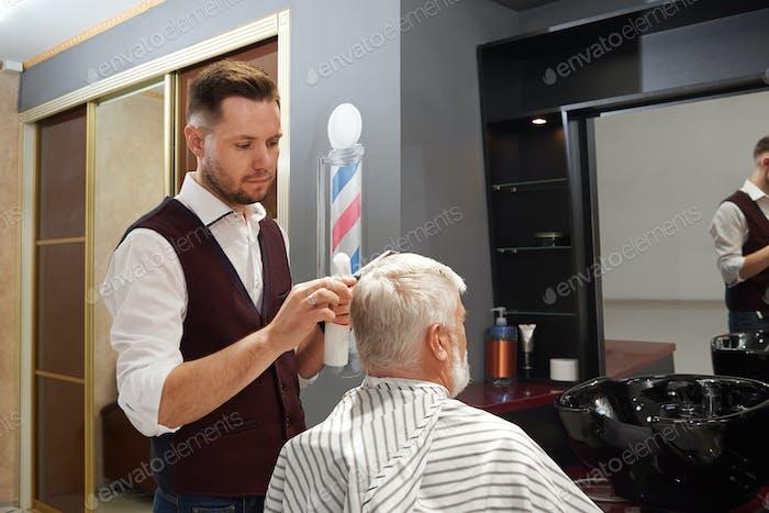 Professional barber grooming man's hair in barbershop