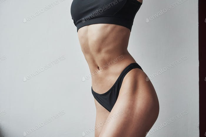 Studio photo. Particle view of hot slim body type of girl that stands in the room