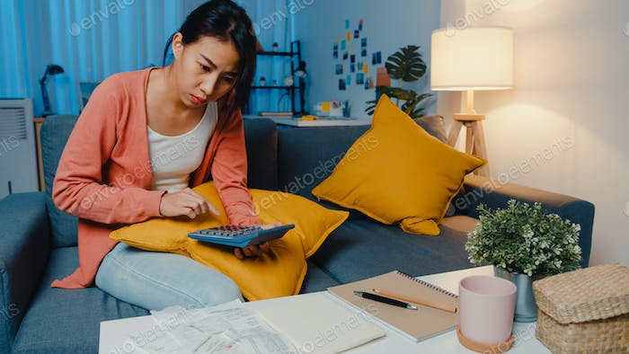 Asian lady feel stress and worried with bill and invoice credit card calculating loan on sofa.