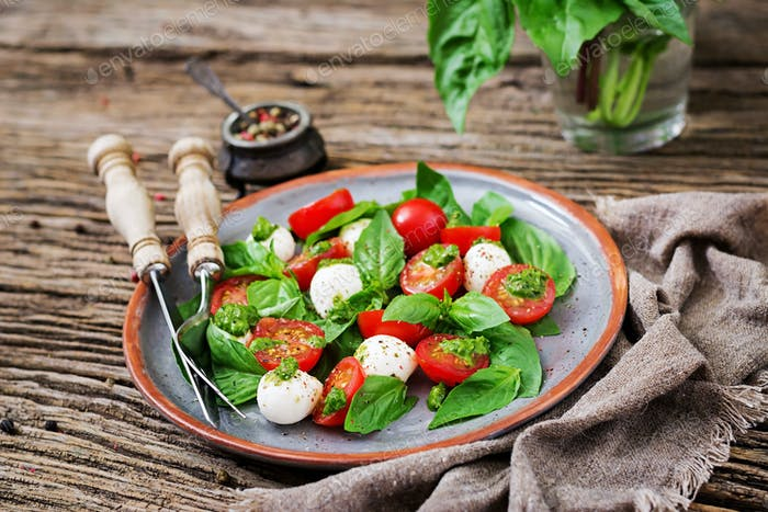 Caprese salad. Healthy meal with cherry tomatoes, mozzarella balls and basil