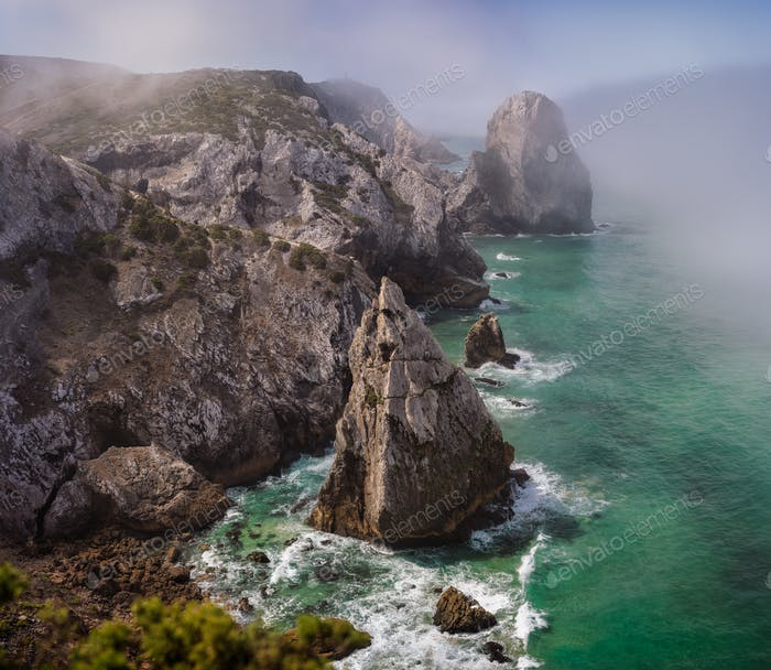 Rocky coastline between Praia Da Ursa and Adraga, Sintra, Portugal. Giant sea stacks towering up