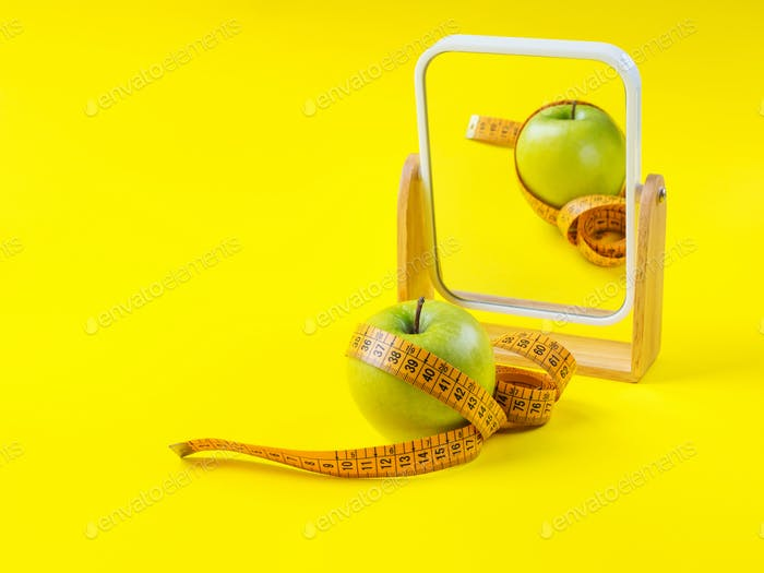 Apple with measuring tape reflected in the mirror