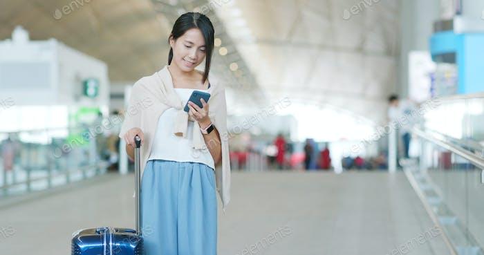 Frau überprüft Flugnummer auf dem Handy im Flughafen