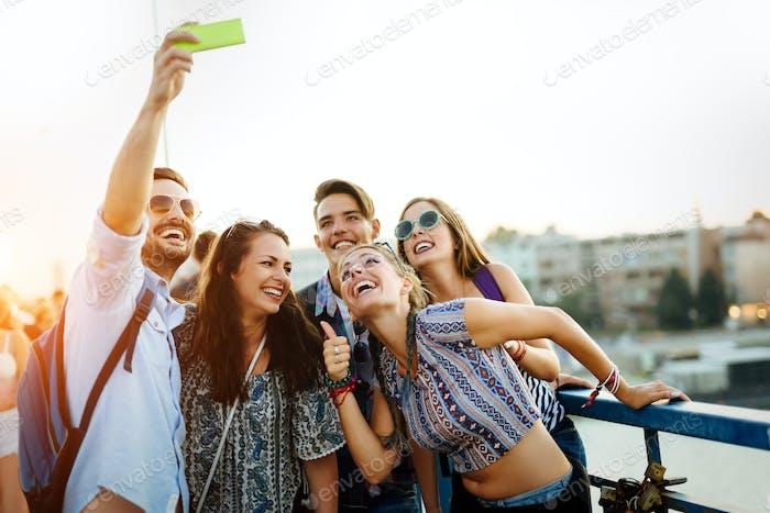 Glückliche junge Freunde nehmen selfie auf Straße
